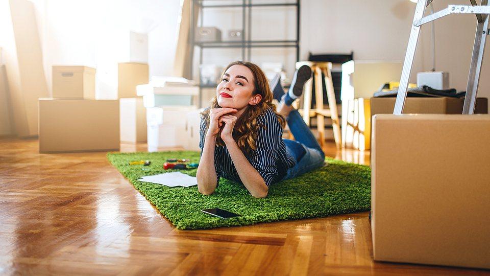 Junge Frau liegt in neuer Wohnung mit Parkettfußboden auf grünem Teppich, Umzugskartons, Leiter, Sessel, Hausratversicherung.
